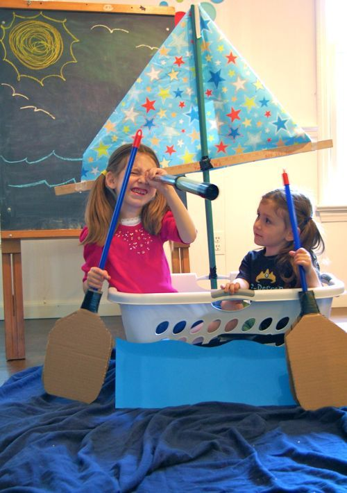 Pretend row boat from a laundry basket and a couple of brooms covered to look like paddles