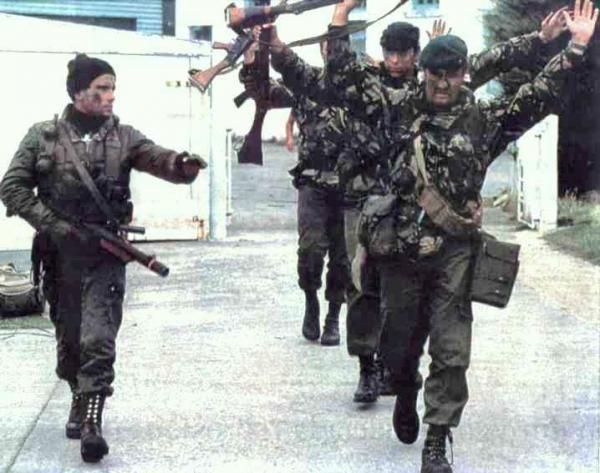 Un cabo de la Agrupación de Comandos Anfibios conduce a un grupo de Royal Marines británicos rendidos en la Operación Rosario, de Reconquista de las Malvinas, el 1 de Abril de 1982