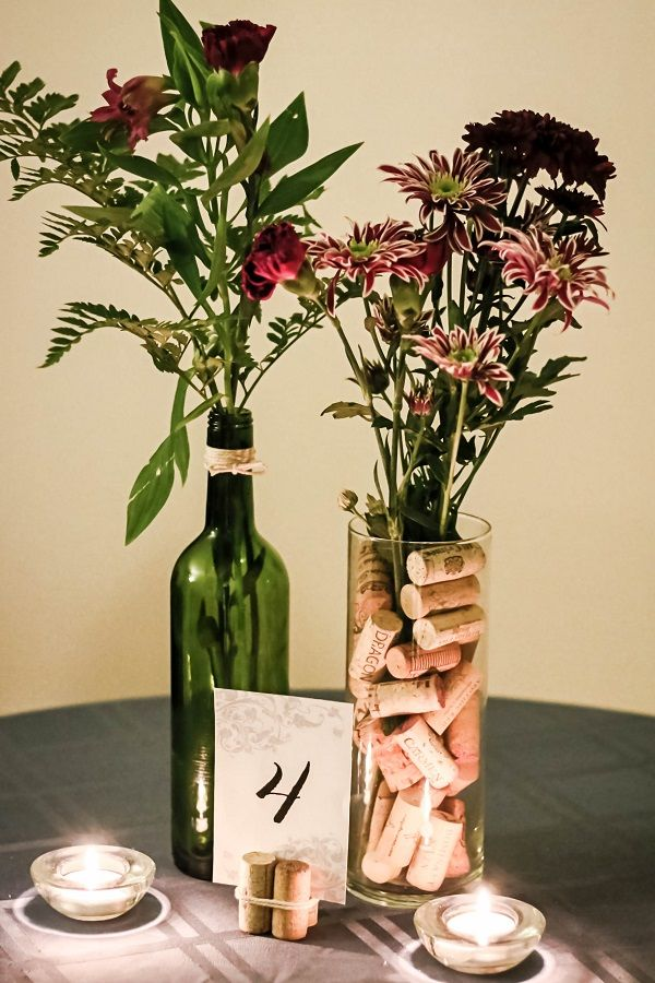 If you're throwing a wine-themed wedding, here's a cheap center piece idea that's environmentally friendly to boot. Collect bottles and corks from your family and friends and you won't have to spend a dime on the bulk of the project! The total cost of one centerpiece as seen above is just under $5!  Supplies:  	A vase (the one displayed is 9 inches tall and 3.25 inches across and is from a dollar store) 	Wine bottle 	Corks 	Roll of twine 	Ruler 	Scissors 	X-acto knife 	Cutting board…