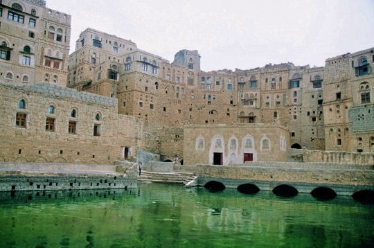 Historic Cistern in Habbaba surrounded by ornamental stone houses, Yemen