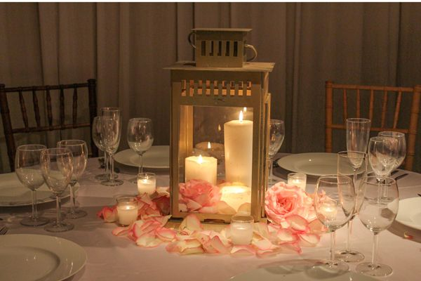 """Centerpieces add up. When deciding on your reception centerpieces, not every table needs a lavish floral arrangement. Candles are a good way to save money. Alternating non-floral centerpieces like floating candles, a cluster of pillar candles in varying heights, mason jars, wine bottles, or fruit arrangements creates an elegant and modern look."""