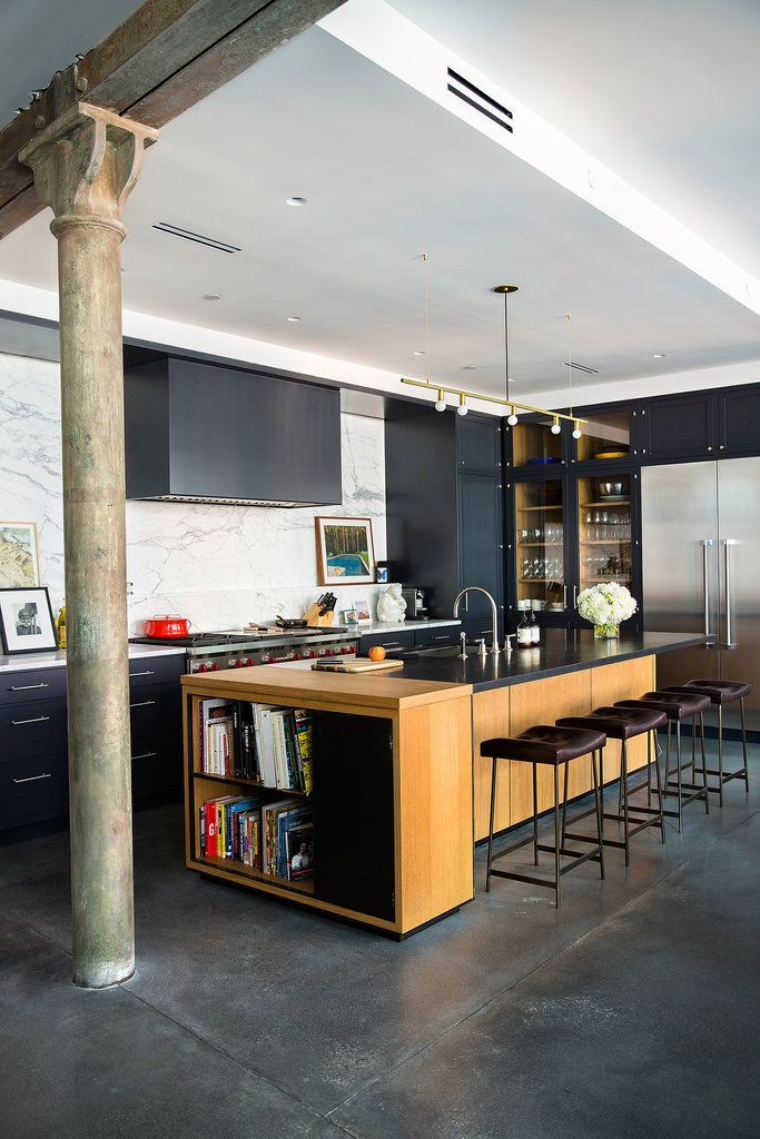 Mr. Zaroff's apartment has newly poured concrete floors. The blackened steel Bunda barstools are from Thomas Hayes Gallery. The light fixture above the island is by Lambert et Fils.
