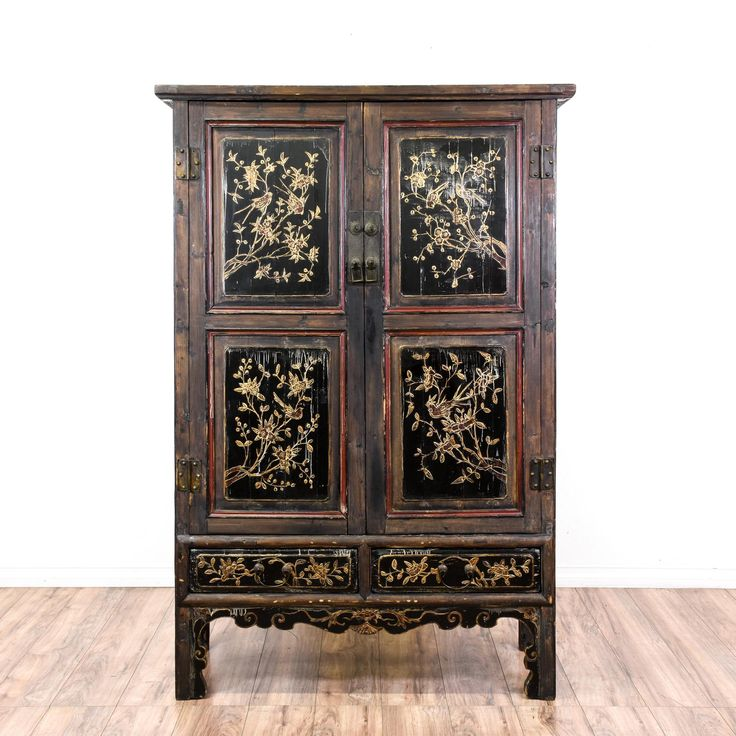 This asian armoire is featured in a solid wood with a distressed black finish and red accents. This large rustic wardrobe has has intricate carved floral and bird details with a large interior cabinet and 4 drawers. Perfect for storing and organizing clothing in a bedroom! #asian #dressers #armoireorwardrobe #sandiegovintage #vintagefurniture