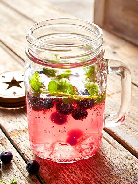 Erfrischender Sommerdrink auf Eis aus Mineralwasser, Zitronenlimo, Blaubeeren und Basilikum. Ein tolle Idee!