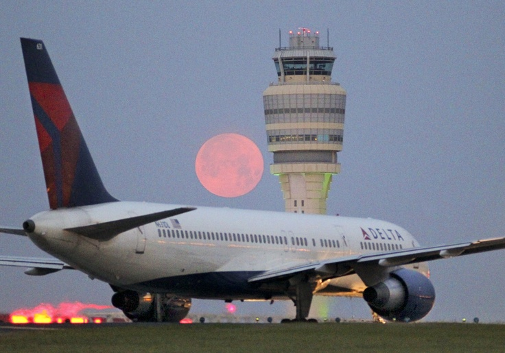 A pink moon looms over the Hartsfield-Jackson International Airport control tower Monday, April, 18, 2011. The Atlanta airport has been the world's busiest airport by passenger traffic since 1998, and by number of landings and take-offs since 2005. Hartsfield-Jackson held its ranking as the world's busiest airport in 2011, both in passengers and number of flights, by accommodating 92 million passengers (252,000 passengers daily) and 923,991 flights.