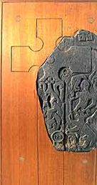 A stone cross from the Isle of Man showing Odin (with raven) fighting the Fenris wolf at the time of Ragnarok