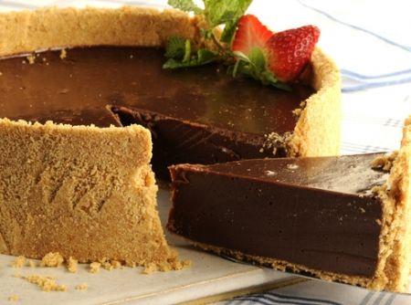 Receita de Cheesecake de Chocolate - 1/2 xícara (chá) de açúcar, 1 1/2 xícara (chá) de biscoito cream craker esfarelado, 100 g de manteiga em temperatura ambiente, 1 colher (chá) de baunilha, 1 lata de leite condensado, 1 copo de requeijão cremoso, 200 g de chocolate meio amargo picado, 1 xícara (chá) de água, 1 envelope de gelatina em pó sem sabor, 1 lata de creme de leite gelado e sem soro