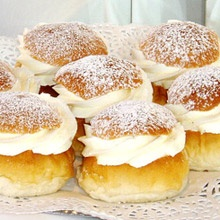 Swedish semla or fetisdagsbulle (Swedish Lent bun). Delicious enriched dough bun, filled with almond paste (mixed with the dough) and topped with whipped cream and icing sugar.