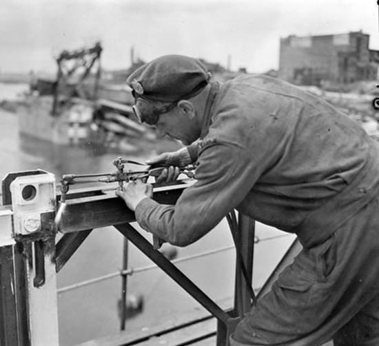 Le Sapeur M.G. Ougler, du 2e Bataillon du Génie canadien, mettant la dernière main à l'un des deux nouveaux ponts construits par le Génie canadien. Le 28 mai 1945 / Zutphen, Pays-Bas.