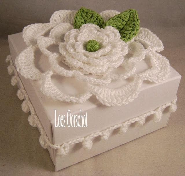 Hier is een cadeautje versierd met een gehaakte bloem.