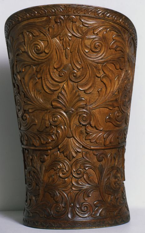 Deze prachtige 'kubbestol' is gemaakt uit één stuk hout. De boom waaruit hij is gezaagd groeide aan de kust ten westen van Kristiansand. Tijdens het transport brak de wagen die hem vervoerde door het gewicht in tweeën. De achterkant en zijkanten zijn uitgevoerd in schitterend acanthus houtsnijwerk. In de onderkant en de rand rond de zitting zijn geometrische patronen uitgesneden. De zitting zelf is uitneembaar. De stoel werd rond 1900 gemaakt door Halvor Lie, een onderwijzer in Kristiansand.