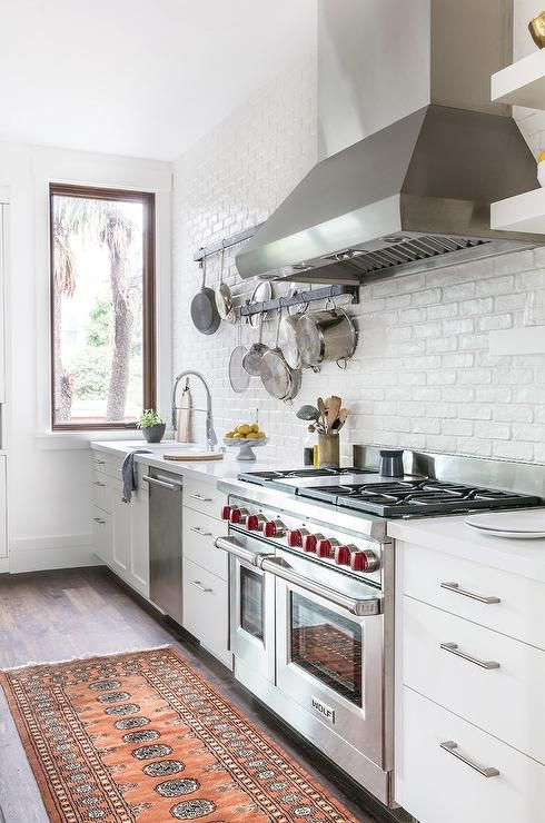 Who doesn't love upgrades? This gorgeous white kitchen features plenty starting with a Wolf dual range oven and stove, stainless steel vent hood and a dishwasher next to the white porcelain sink with a stainless steel pull out faucet.