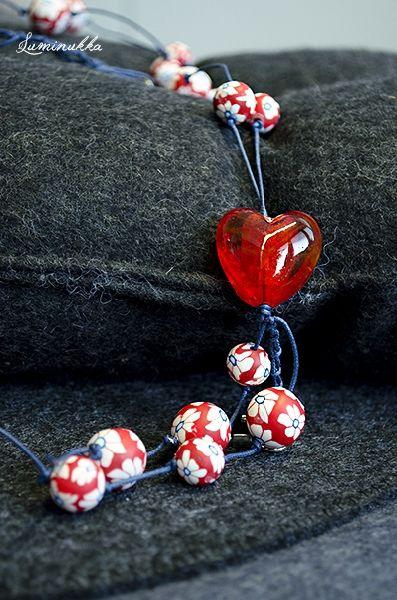"""Kesäkimara, avainnauha kumimaisia, erikokoisia kukkapalloja ja iso lamppuhelmisydän tummansinisessä nauhassa  """"Summer Cocktail"""", lanyard Different sizes of rubbery flower balls and one big red lampworked glass heart"""