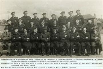 Clydebank ARP Wardens Front Row - W. McFarlane, J. Longde, Mrs. J. Hyslop, R. Turner, C.D., H. Kelly, A. Cameron, Inspector A. Macdonald, Div. Wards. C. MacKenzie (B), W. Laurie (D), W. Bowie (D). Second Row - Sen. Ward. A. Little, Head Wards. E. Connell, H. Brown, Div. Wards. R. Baird (A), T. H. Overend (C), Head Ward. T. Rae, Sen. Ward. S. McLintock, Head Ward. J. Menzies. Back Row - Sen. Wards. D. Rendall, P. Wallis, W. Ross, R. Caldwell, D. McMillan, E. Brash, A. McKellar, J. Johnston…