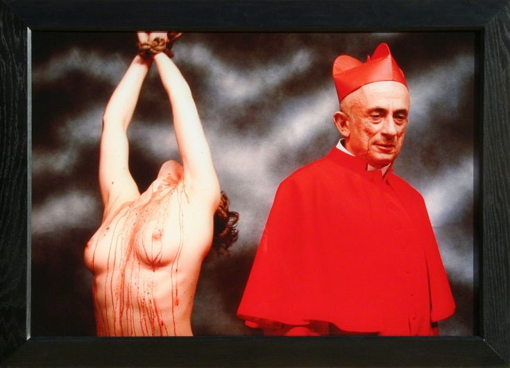 """Andres Serrano. """"In Heaven and Hell, Andres Serrano challenges the benevolence of the Catholic Church while also taking on the sexualization of violence against women. The work was made in collaboration with political artist Leon Golub, who appears in the photograph wearing the red robes of a Cardinal, subtly smiling as he looks away from the blood-splattered nude who is bound and suspended next to him."""