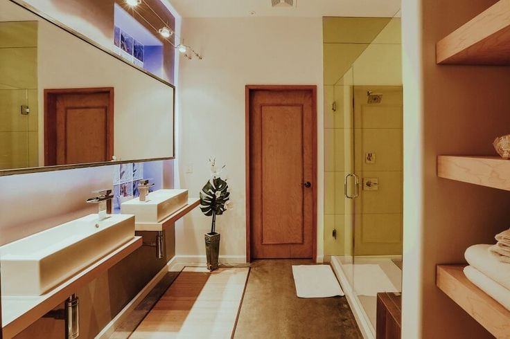 Nestled within a grand open-plan home, this bathroom is awash in warm neutral tones. A glass enclosed walk-in shower stands at right, across from a pair of discrete vanities with vessel sinks.