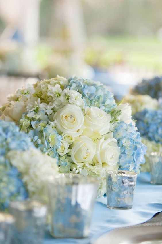 Pretty spring wedding centerpieces with white roses and light blue hydrangeas