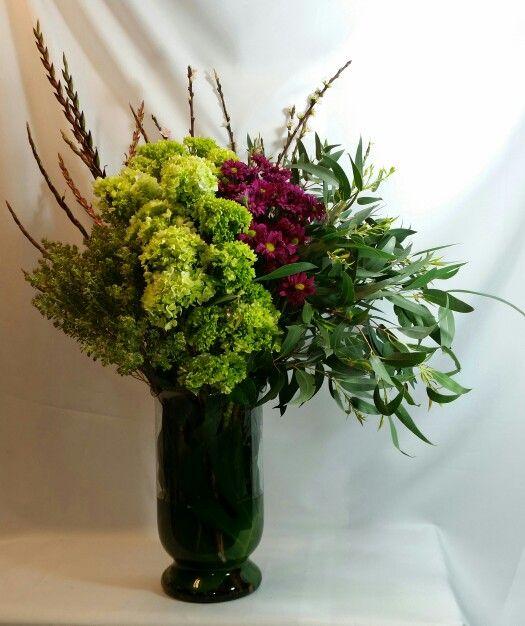Arreglo de hortensias verdes, margaritas rojas y follajes