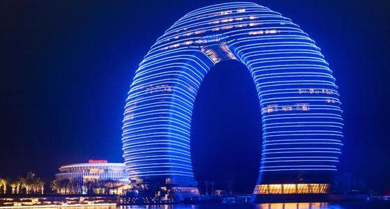 """3. Sheraton Huzhou Hot Spring Resort (Huzhou, China). También recién salido del horno es este otro """"humilde"""" hotel chino cuyo nombre se las trae. La forma elegida fue algo así como una herradura anillada de 100 metros de alto y 116 metros de ancho anclada en la orilla sur del lago Taihu, en la ciudad de Huzhou. El contraste entre su silueta futurista que de noche se tiñe de colores eléctricos y el paso entre la niebla de las tradicionales embarcaciones pesqueras es más que surreal."""