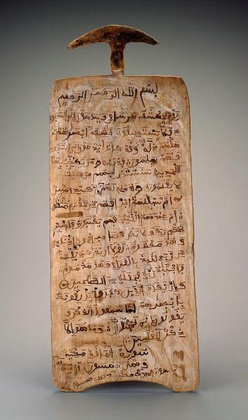Africa | Koranic writing board. Hausa peoples, Nigeria | Mid to late 20th century | Wood, ink, hide | Wooden writing boards, some of them embellished with magic squares and other non-figurative designs in addition to Koranic script, serve to illustrate the long history of Islam and literacy in Africa. The boards are most often used by young Moslem students who are learning to read, write and recite Sura or passages from the Koran, Islam's sacred book.