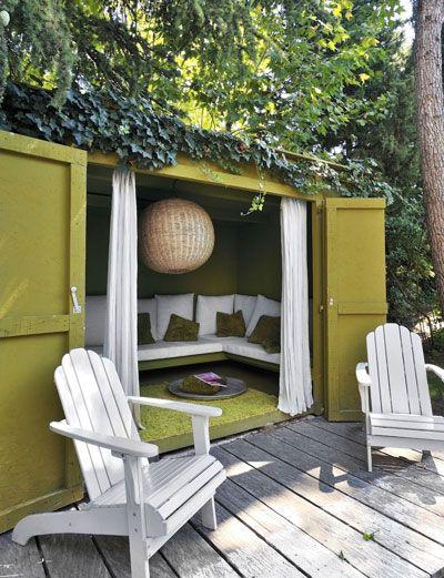 Tuinhuis wordt loungehoek met een bank, vloerkleed, sfeerlamp en gordijnen.