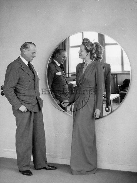Kurt Jacobsson på NK:s franska skrädderi tillsammans med mannekäng i lång aftonklänning. 1950-talet.