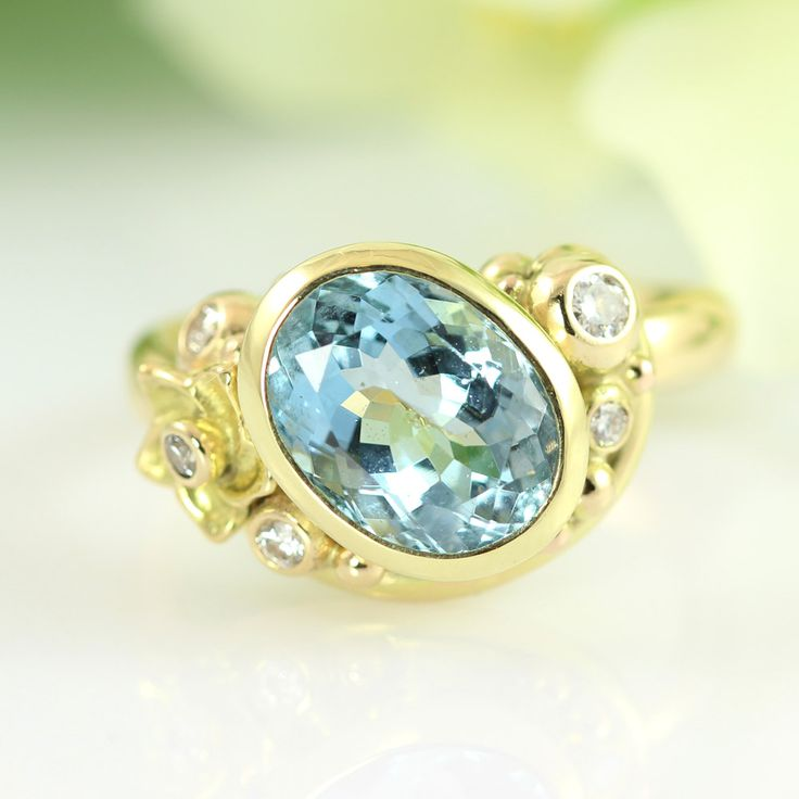 Handcrafted gold ring with aquamarine Wonderful renewal and recycling of an old gold ring! The beautiful blue aquamarine glitters surrounded by the warmth of the 14k gold and a team of diamonds. A small flower provides the finishing romantic touch.