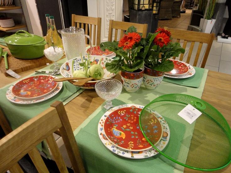 Czerwcowy stół idealnie nadaje się do serwowania szparagów i truskawek. Zamiast obrusu użyjemy seledynowego bieżnika i ciemniejszych podkładek, aby odsłonić piękne drewno dębowe. Przyciągającym akcentem będzie kolorowa ceramika Paradise zdobiona ludowymi, szwedzkimi wzorami. Pojemne kubki tym razem wykorzystujemy jako wazony podkreślające żywy kolor kwiatów.