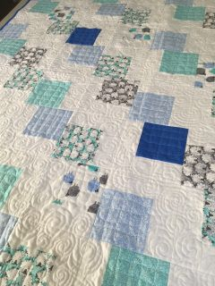 This baby or toddler quilt features whimsical sheep in blues, aqua and grey.