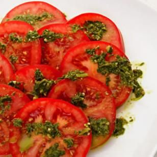 Sliced Tomatoes with Pesto Drizzle    Prepared pesto whisked with a little vinegar makes the perfect dressing for sliced ripe tomatoes.
