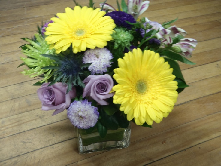 Sunshine yellow gerbera paired with lavender roses, blue thistle and lime green fuji's