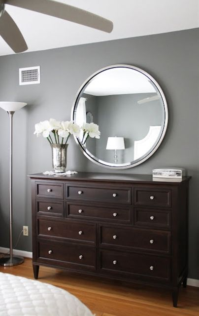 master bedroom...love the paint color, dark wood and style of the dresser and round silver mirror. So beautiful. very modern looking.