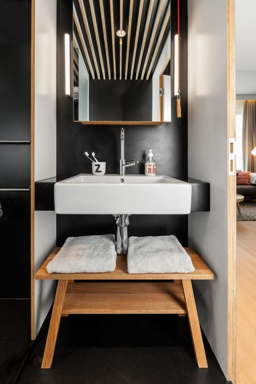 ZOKU LOFT AMSTERDAM: IL BAGNO Il bagno, situato accanto all'ingresso, contiene un armadietto dei medicinali collocato sopra il lavabo in ceramica e un vaso sospeso. La doccia nel retro può essere separata dalla zona lavabo/toilette da una porta di vetro sabbiato. La parete posteriore della doccia è completamente rivestita in specchio per duplicare la dimensione dello spazio.