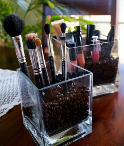 Vases filled with coffee beans to hold makeup items. Love it!