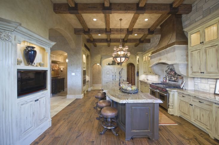 Massive country kitchen design in white, grey and wood.  Elevated wood-beamed ceilings caps white ornate cabinets, grey island and wood floor