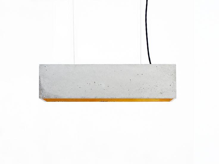 Die rechteckige Pendelleuchte B4 wird aus Beton gegossen. Sie vereint edles Gold mit rauem Beton zu einer zeitlosen und eleganten Designerleuchte. Durch die hochwertige Vergoldung der Innenseiten gibt sie ein angenehm warmes Licht ab.