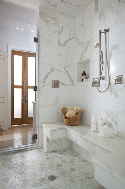 source: Denman Bennett   Amazing master bathroom shower features statuario marble shower surround accented with niche holding bath accessories and U shaped marble shower bench over calcutta gold marble hex tile shower floor.