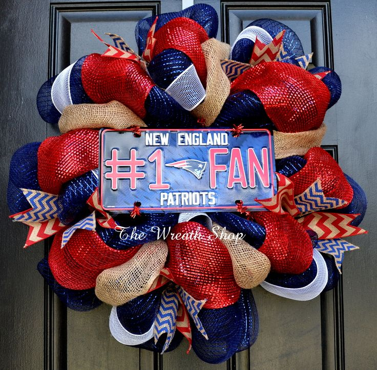 Show your Patriots Pride with this New England Patriots mesh wreath made on a navy blue deco poly mesh. It is accented with red mesh and burlap, coordinating chevron ribbons, and white mesh. The centerpiece is a metal Patriots