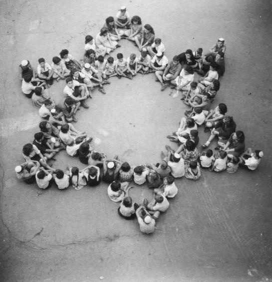 What an unbelievable picture...this is children who survived the Buchenwald concentration camp sitting in a Jewish Star, what a powerful memory!