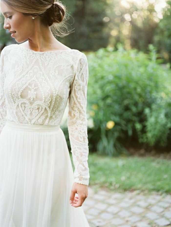semi close up of a blonde bride in a white dress with embroidered top and plain bottom, with a simple hair knot, trees and bushes in background