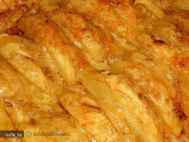 Curatati cartofii de coaja si taiati-i in fasii groase, pe lungime. Puneti-i la fiert intr-un vas cu apa fierbinte sarata, doar pentru 5 min. Scurgeti imediat. Asezati-i aliniati intr-un vas termorezistent (tava) tapetat cu ...