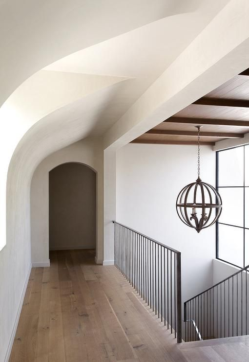 Mediterranean home features an iron staircase railing illuminated by a wood sphere pendant.