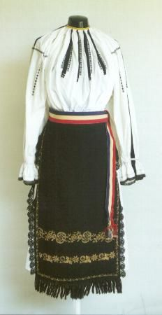 Romanian Women's costume from county of Sibiu  Blouse (ie) made of white cotton, decorated with black embroidery called Punctul 'Ciocănele'  which gives the appearance of vertical bands of  black braid on the sleeves and front of the blouse.