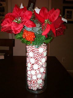 Florist's vase with peppermints and faux stems of Christmas flowers.