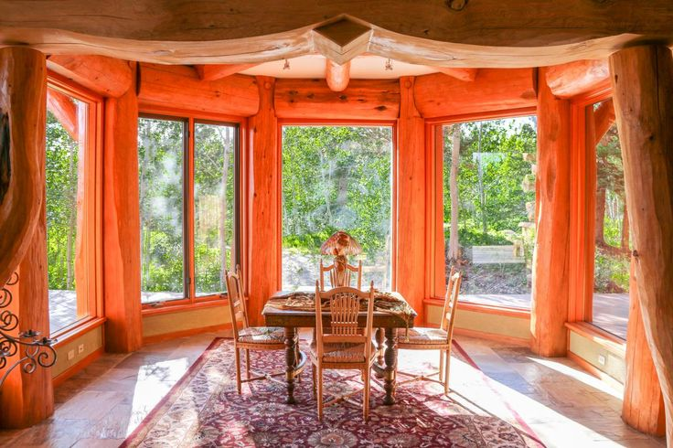 Also located in the tower house, the dining room features floor-to-ceiling windows with beautiful views of outdoor scenery. A small wood dining table pairs with four modest chairs for a cozy, intimate feel.