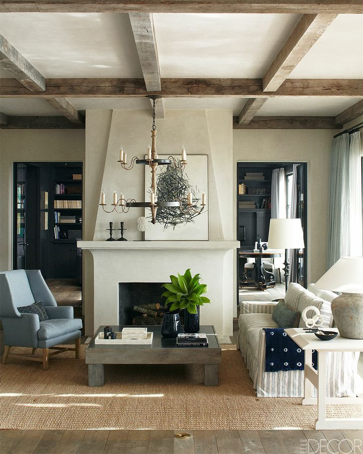 Great fireplace in centre of room, library on back wall?, exposed beams enhancing a rustic feel