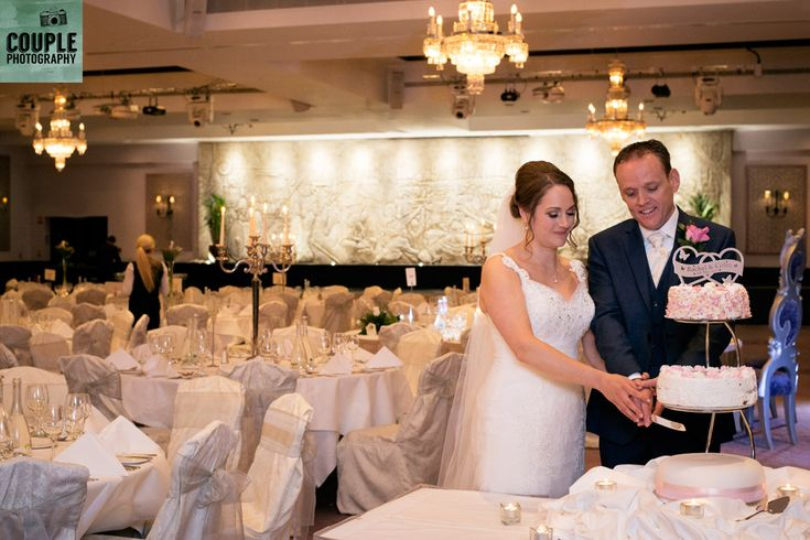 The bride & groom cut the cake in the main hall. Weddings at Clontarf Castle Hotel by Couple Photography.