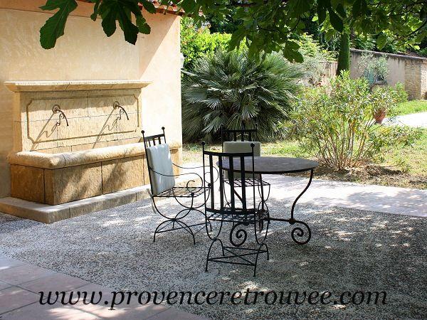 Fontaine murale en pierre à la terrasse d'un mas provençal.