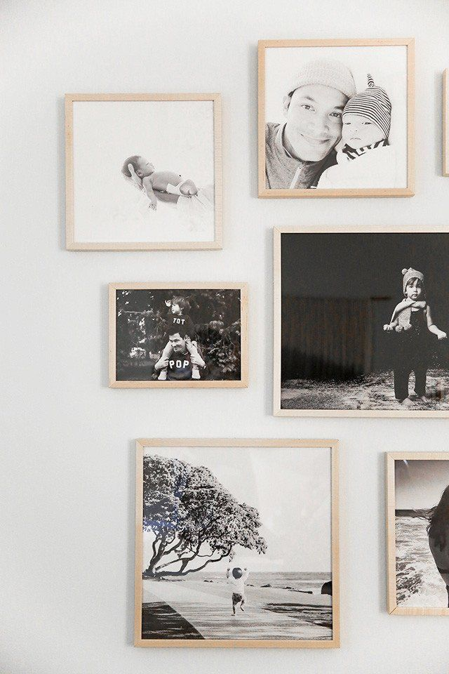 A bedroom gallery wall of black and white family photos in Simply Framed Natural Gallery Frames by photographer Max Wanger.