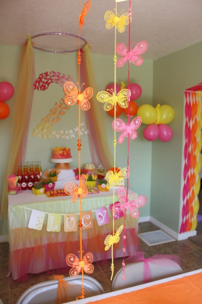 Butterfly Themed Party - Sparkly Butterfly garlands dangling from dining room chandelier - eventstocelebrate.net